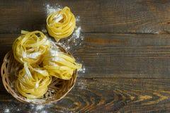 Итальянское tagliatelle макаронных изделий в корзине на таблице с мукой стоковое изображение