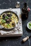 Итальянское tagliatelle макаронных изделий с одичалыми грибами в сковороде и пиве на темной предпосылке Стоковые Фото