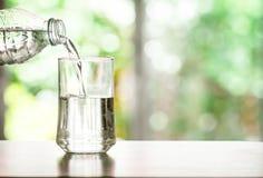 лить очищенная свежая вода питья от бутылки на таблице внутри Стоковая Фотография RF