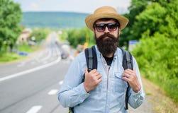 Ищите попутчики Подсказки опытного backpacker Укомплектуйте личным составом бородатый backpacker битника на крае шоссе Выберите м стоковые изображения rf