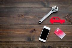 Ищущ обслуживание автомобиля онлайн Вычисление цены Оплата для ремонта автомобиля Силуэт автомобиля, ключ, сотовый телефон, банк Стоковая Фотография RF