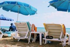 Июль 2017 - остатки людей на deckchairs в тени зонтиков пляжа на пляже Alanya Cleopatra, Турции Стоковое Фото