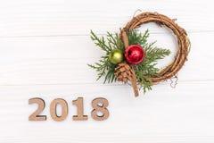 2018 и венок ветви и конуса сосны на белой деревянной предпосылке Стоковая Фотография RF