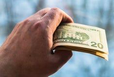10 и двадцатидоллоровые банкноты в руке человека на запачканной предпосылке Концепция, финансы, кредит стоковые фотографии rf