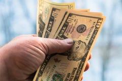 10 и двадцатидоллоровые банкноты в руке человека на запачканной предпосылке Концепция, финансы, кредит стоковое изображение rf