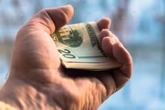 10 и двадцатидоллоровые банкноты в руке человека на запачканной предпосылке Концепция, финансы, кредит стоковое изображение