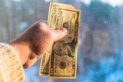 10 и двадцатидоллоровые банкноты в руке человека на запачканной предпосылке Концепция, финансы, кредит стоковые фото