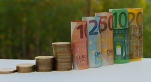 10, 20, 50, 100, 200 и евро монеток свернули банкноты счетов на запачканной зеленым цветом предпосылке bokeh Гистограмма fr Стоковое Изображение RF