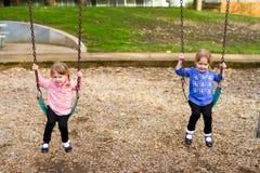 Идентичные близнцы на парке на качаниях Стоковая Фотография RF