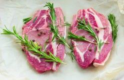 2 идентичных стейка от свинины с специями и розмариновым маслом на бумаге Стоковое Фото