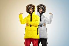 2 идентичных snowboarders указывая в различные направления Стоковое фото RF