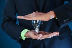 Идея дела. Бизнесмен держа электрическую лампочку. Стоковое фото RF