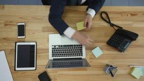 Идея сочинительства работника офиса на стикере и методе мозгового штурма на рабочем месте, взгляд сверху сток-видео