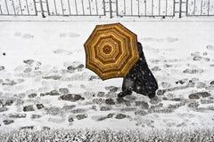 Идите на тротуар с зонтиком в снежностях Стоковые Изображения