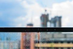Идите дождь падения на стеклянных балконе и конструкции в предпосылке Стоковые Изображения RF