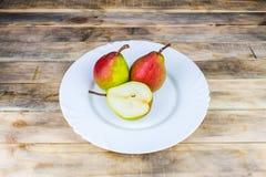 2 и половинные груши в белой плите, деревенском деревянном столе Стоковая Фотография