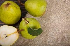 3 и половинные груши на деревянных предпосылке и мешковине Стоковая Фотография