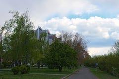 Идти в старый парк Новые многоэтажные здания видимы за деревьями kiev Украина Стоковое Изображение