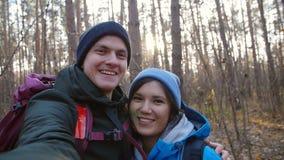 И укладывая рюкзак концепция Молодые счастливые пары с рюкзаками в лесе и selfie делать видеоматериал