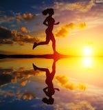 Идущая девушка на силуэте захода солнца Стоковое фото RF
