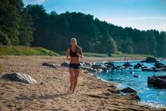 идущая женщина Женская разминка бегуна на пляже Стоковые Фото