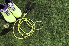 Идущие ботинки, веревочка скачки и бутылка питья с зеленым соком Стоковые Изображения