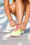 Идущие ботинки - женщина связывая шнурки ботинка Крупный план женского спорта Стоковая Фотография