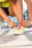 Идущие ботинки - женщина связывая шнурки ботинка Крупный план женского спорта Стоковое фото RF