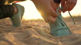 Идущие ботинки - женщина связывая шнурки ботинка на песчаном пляже на заходе солнца сток-видео