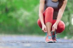 Идущие ботинки - крупный план женщины связывая шнурки ботинка Стоковые Фото