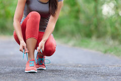 Идущие ботинки - крупный план женщины связывая шнурки ботинка Стоковое фото RF