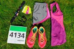 Идущие ботинки, номер bib гонки марафона, бегуны зацепляют и гели энергии на предпосылке травы, спорте, фитнесе стоковое изображение