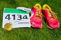 Идущие ботинки, bib гонки марафона (номер) и медаль фертиг-аппарата на предпосылке травы, стоковые фото