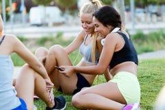 Идущие девушки имея потеху в парке с мобильным телефоном Стоковая Фотография