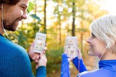 Идущие пары с умными телефонами и наушниками Стоковая Фотография RF