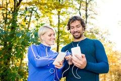 Идущие пары с умными телефонами и наушниками Стоковые Фотографии RF