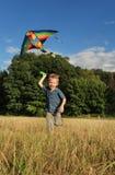Идущий мальчик с змеем летания Стоковые Фотографии RF