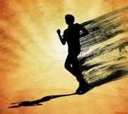 Идущий силуэт черноты человека на оранжевой предпосылке Стоковая Фотография