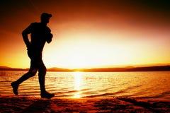 Идущий человек на пляже Спортсмен бежит в capr бейсбола, jogging парень во время восхода солнца Стоковое Фото