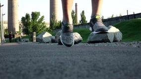 Идущий человек jogging в конце парка вверх обуви ботинок в траве в парке конец вверх движение медленное