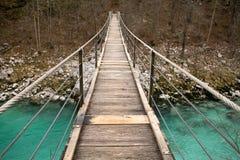 Идущ на деревянный footbridge пересекая над рекой бирюзы soca, национальный парк triglav, Словения Стоковые Изображения