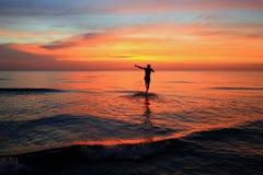 Идя человек на пляже на красочном заходе солнца Стоковая Фотография RF