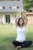 йога азиатской беременной женщины практикуя на зеленой траве перед Стоковое Фото