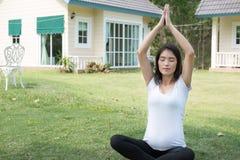 йога азиатской беременной женщины практикуя на зеленой траве перед Стоковая Фотография RF