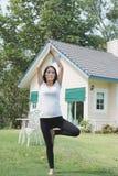 йога азиатской беременной женщины практикуя на зеленой траве перед Стоковые Фото