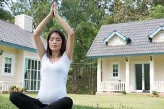 йога азиатской беременной женщины практикуя на зеленой траве перед Стоковая Фотография