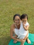 Йога азиатской китайской женщины практикуя outdoors с молодым gir младенца Стоковое фото RF