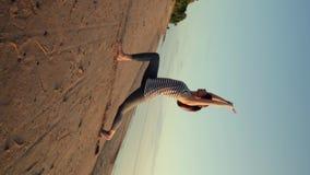Йога активной молодой женщины протягивая и практикуя на пляже на заходе солнца сток-видео