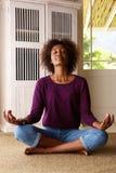 Йога Афро-американской женщины практикуя дома Стоковое фото RF