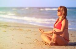 Йога беременной женщины практикуя на пляже стоковое изображение rf